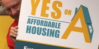 """Chris Wilder, Valley Medical Center Foundation CEO, holds a sign that reads """"Yes on A: Affordable Housing. Everyone should have the opportunity to live in a safe, healthy, affordable home."""" The initiative tied health and housing funding for county residents."""