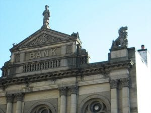 The spires and statue atop an old bank building.