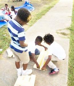 3 children measuring a board laid on a sidewalk.