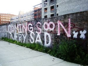 """""""Coming Soon, Very Sad"""" painted on border wall outside of new development."""