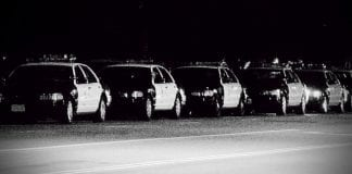 Black and white photo of a row of police cars.