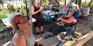 Three women sitting on chairs on a sidewalk.