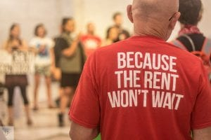 """Close-up of the back of a T-shirt that says """"Because the rent won't wait."""" Ways to help with the high cost of rent include rent control, rental assistance, and universal vouchers."""