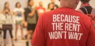 """Close-up of the back of a t-shirt that says """"Because the rent won't wait."""""""