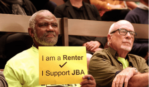 """Man holding a yellow sign that reads """"I am a Renter/I Support JBA"""""""