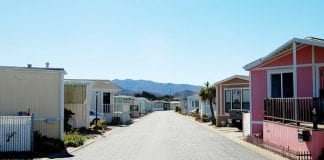 Row of trailer homes with mountains in the background.