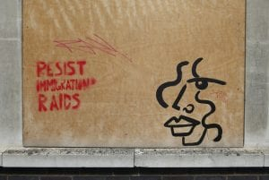 """Boarded window with """"Resist Immigration Raids"""" sprayed on it, referring to ICE raids."""