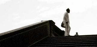 Man with a cane stands at the top of set of stairs in a park .