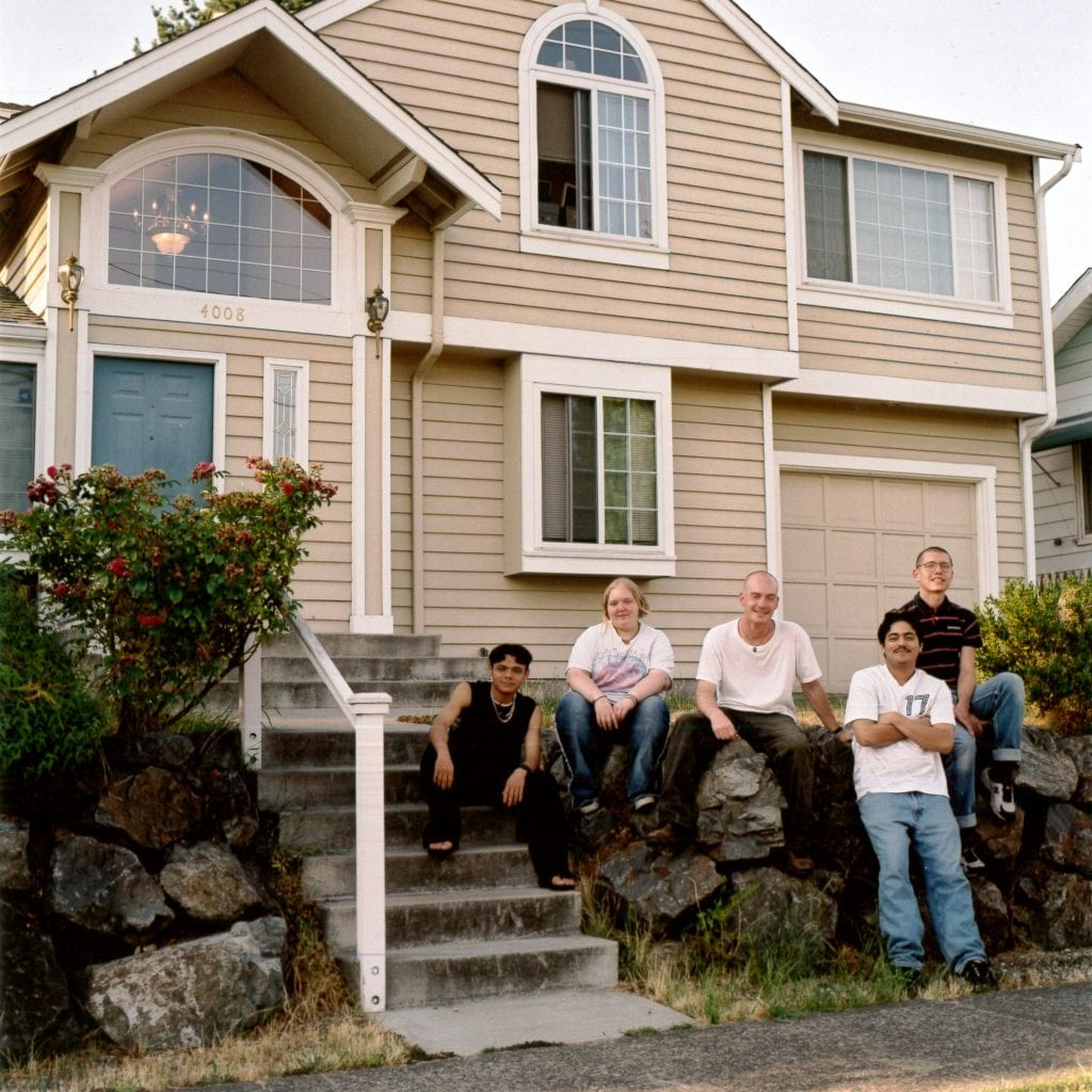 A group of people stand outside a home used for transitional housing after it lost funds due to the City of Seattle diverting resources to rapid re-housing.