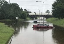 A car and truck submerged on a flooded road.