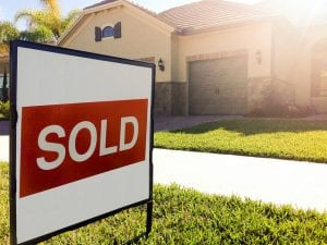 A home with a sold sign in front to illustrate tax reform related to housing.