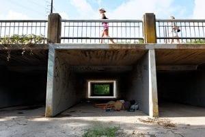 Two people sleeping beneath a pedestrian overpass in Bouldin Creek, Austin. A person walks above.