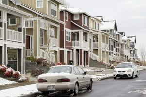 A line of homes in Seattle, Washington. Two cars are also shown.