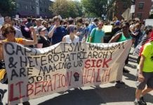 """Members of Boston Liberation Health hold a banner that reads, """"Capitalism, racism, and heteropatriachy are making us sick. Join Liberation Health."""""""