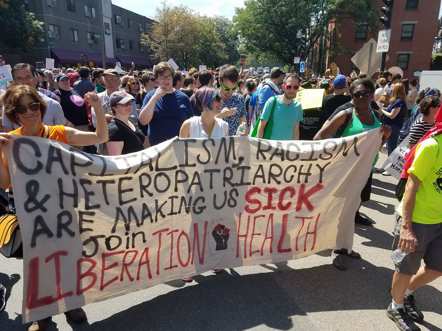 """Members of Boston Liberation Health hold a banner that reads, """"Capitalism, racism, and heteropatriachy are making us sick. Join Liberation Health."""" The group are advocates of social justice, human liberation, and mental health."""