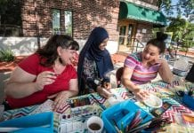 Three Minneapolis residents chat while sitting at a table outdoors.