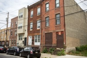 A solid-looking rowhouse in Philadephia that is surrounded by homes that are in need of repairs.