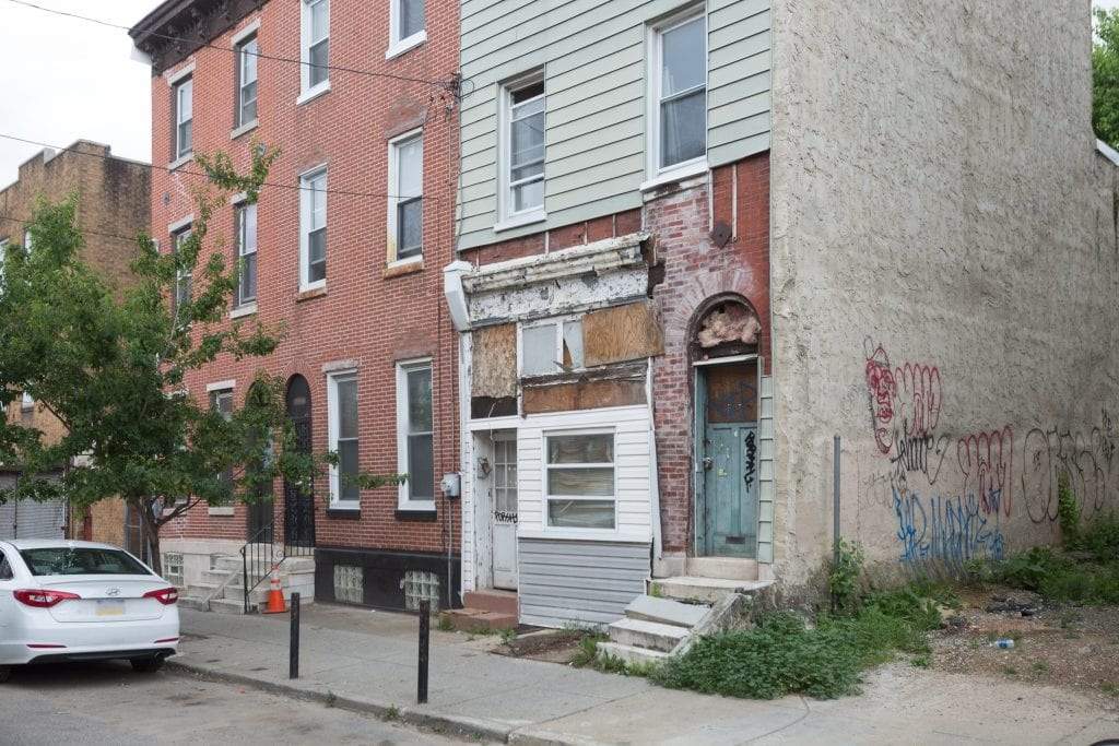 An exterior view of a rowhouse in Philadelphia, Pennslyvania that appears to have some water damage and needs repairs.