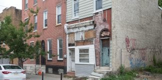 An exterior view of a rowhouse in Philadelphia, Pennslyvania that appears to have some water damage.