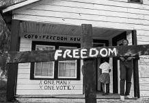 """A historical photo of a burned cross with the word """"Freedom"""" in white across it."""
