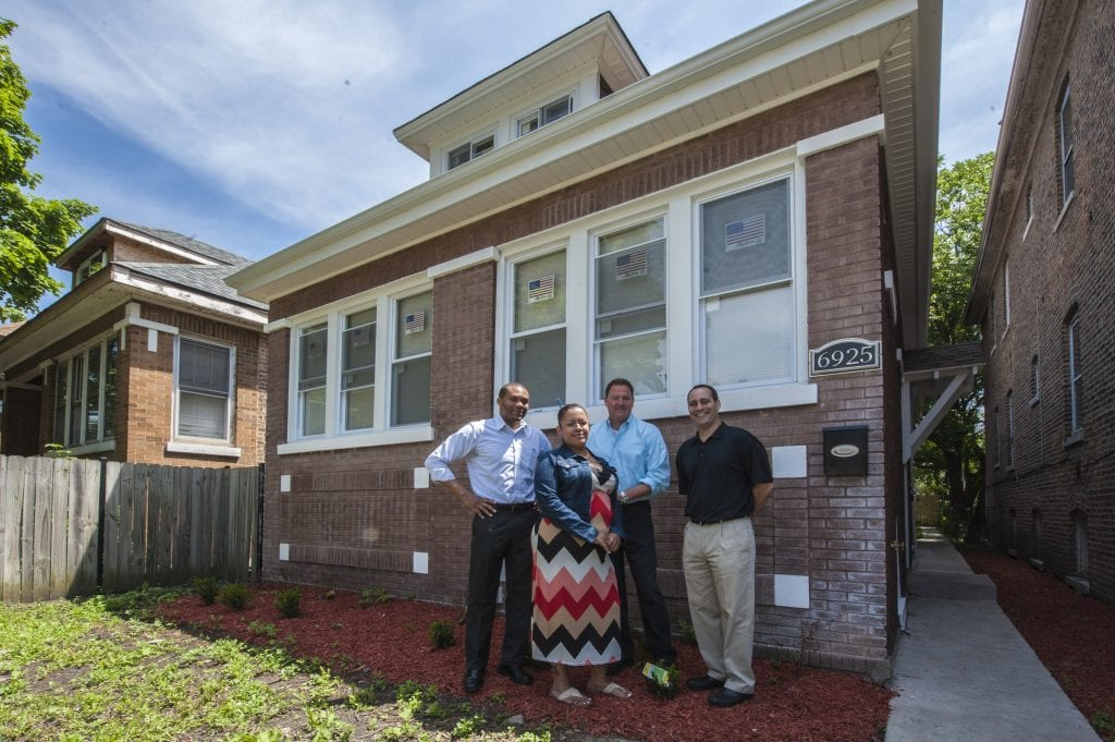 A group of people stand in front rental housing in Chicago that was rehabbed.
