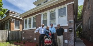 A group of people stand in front of a Chicago home that was rehabbed.