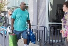 An African-American man in blue T-shirt and shorts, carry full shopping bags approaches the top of a ramp, where he is greeting by a white woman in a multicolored blouse. Two other people with belongings follow him up the ramp.