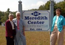3 women posed at the sides of a sign.