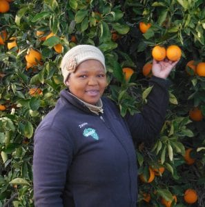 Woman posed in front of an orange tree.