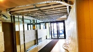 Lobby with plastic sheeting and exposed ceiling.