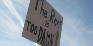 """A sign that reads """"the rent is too damn high."""""""