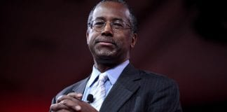 HUD Secretary Ben Carson smiles as his folds his hands in front of his chest.