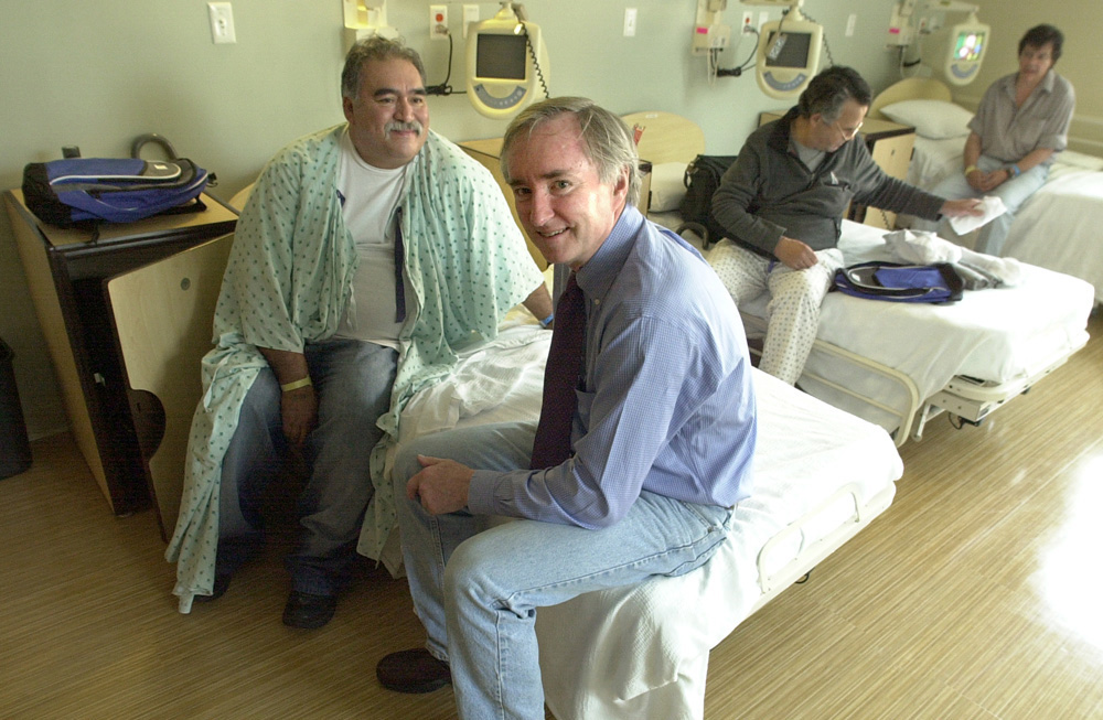 Dr. Jim O'Connell sits on a patient's bed at Pine Street Inn Supportive Housing in Boston.