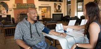 An African-American man gets his blood pressure checked at the California Hotel, an EBALDC development that offers affordable apartments with community and commercial spaces.