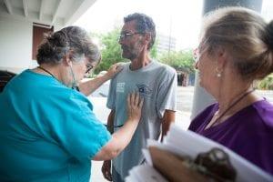 A woman checks a homeless man's heart rate.