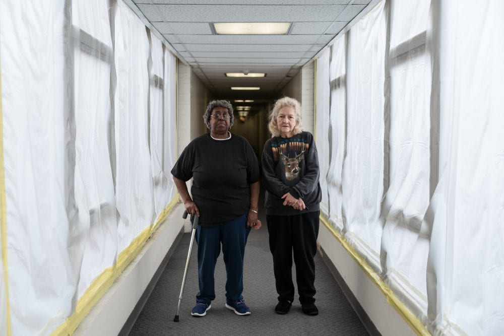 Two older women stand side-by-side in a corridor in a building in Pittsburgh.