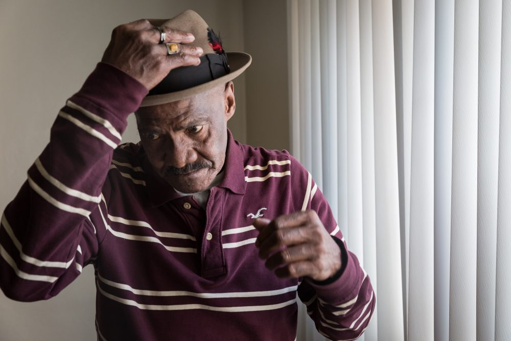 An older African-American man puts on his hat in his Pittsburgh apartment.