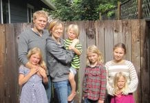 A husband and wife stand in front of a fence along with their five children.