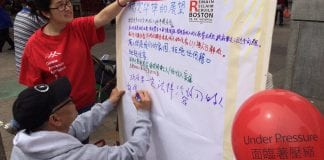 Two people write down thoughts about what they think Chinatown's future should be.