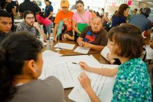 Houston residents gather around a large table to discuss ideas to improve their neighborhood.