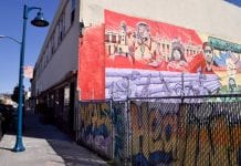 A building in East Oakland with colorful murals painted on the wall. A graffitied fence is to the right of the building.