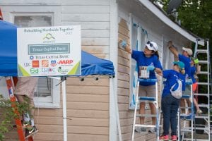 Five people wearing blue shirts paint the side of a home.