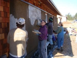 Ccontractor, resident, interns and volunteers worked together to put on a lime coat on the straw-bale wall.