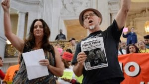 """Carin McKay and Chris Carlsson at City Hall during a Mission No Eviction protest in 2015. Charlsson holds a sign that reads """"We support the Pigeon Palace becomming a SF Community Land Trust."""""""