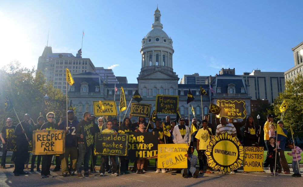"""A group of people with yellow and black signs stand outside of Baltimore's City Hall. Some signs read """"Respect for All,"""" """"Living Wages Now,"""" and """"Sueldos Justos Ahora."""""""