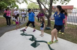 Several residents, as well as some children, enjoy outside exercise equipment.