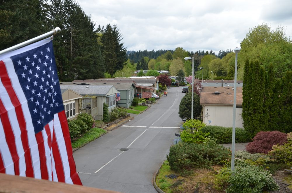 A view of a community in Oregon, with an American flag framing the left hand side. Lots of trees in the area.