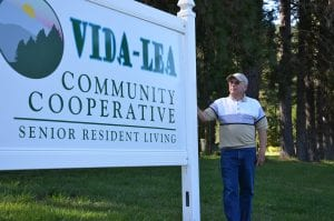 """A white man stands near a sign that reads """"Vida-Lea Community Cooperative Senior Resident Living."""""""
