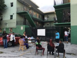 A group of people gather outside an apartment complex to discuss community land trusts.