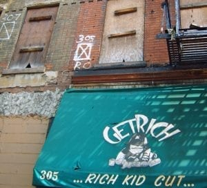 """A vacant building in New York City that has boarded up windows and a """"Get Rich"""" signs for a kid cut."""